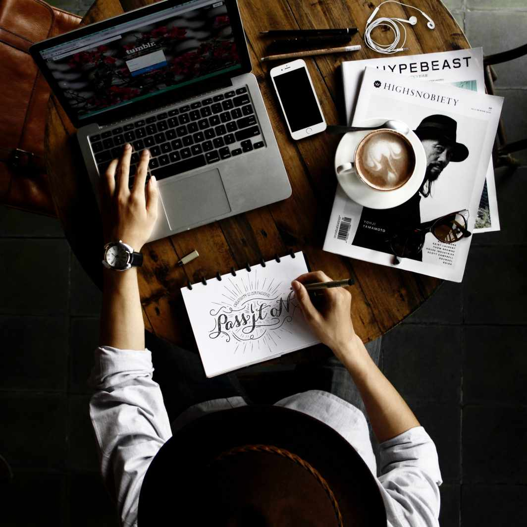 Top view of a person outsourcing graphic design in a laptop, notebook, magazine, and coffee. -