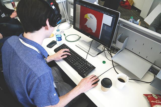 A man working on a PC designing an eagle that shows Graphic Design Outsourcing.