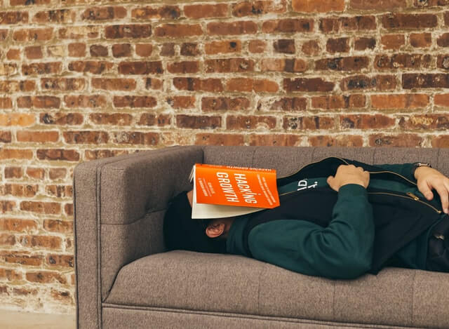 """A growth hacker fell asleep on a couch with a book titled """"Growth Hacking"""" on his face."""